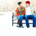Portrait of a lovely young couple sitting on a bench outdoors during winter season