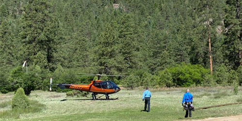Helicopter waiting for passengers in a field