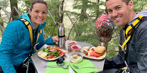 A couple eats lunch on an elevated platform while zip lining at Soaring